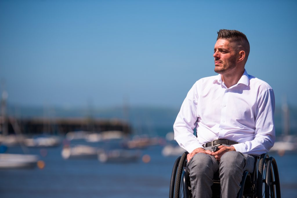 Micheal Kerr sits in his wheelchair. In his hand is a black WheelAir remote. He is wearing grey trousers and a white collared shirt. In the background is the sea with sailboats floating in the water.